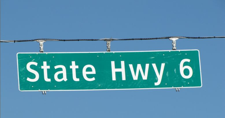 State-Hwy-6-signage-long-green-street-name-panel-hanging-from-wire-across-the-road