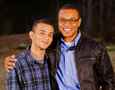 Portrait of African-American father and teenage son outdoors at park
