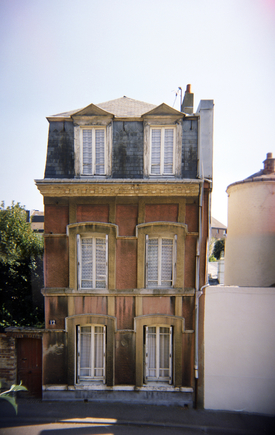 A stock photograph of a quaint and tall three story European house.